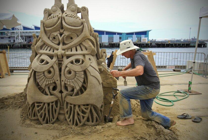 Kirk Rademaker, works on his entry, Bug on a Rug, during the U. S. Sand Sculpting Challenge.