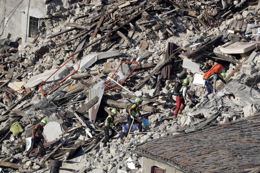 Rescatistas avanzan entre los escombros de viviendas tras un sismo en Pescara Del Tronto, en el centro de Italia. El terremoto de magnitud 6,2 registrado la víspera causó centenares de fallcidos y cuantiosos daños materiales. (AP Foto/Gregorio Borgia)