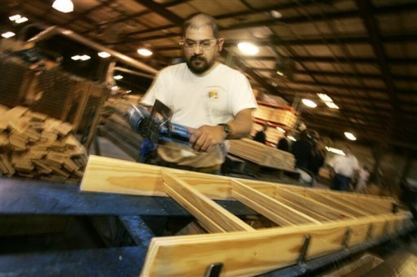 In this photo taken Dec. 21, 2009, a worker assembles a wooden folding ladder at the Century Industries Folding Attic Stairways plant in Little Rock, Ark. Worker productivity rose more than expected in the October-December quarter as companies squeezed more output from their employees.(AP Photo/Danny Johnston)