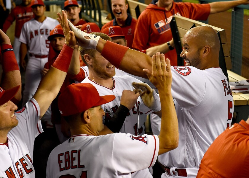 Albert Pujols celebrates with his teammates after a first-inning home run Monday against Cincinnati.