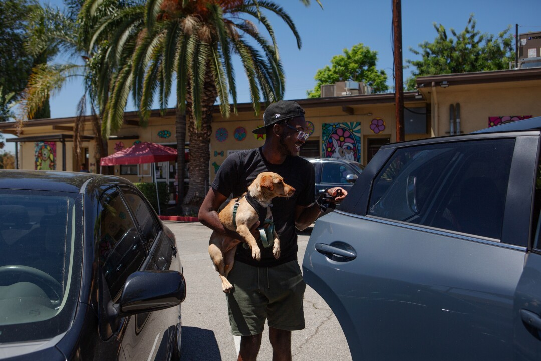 Kavar McDaniel carries his newly adopted dog to his car outside a Los Angeles County Animal Care and Control shelter.
