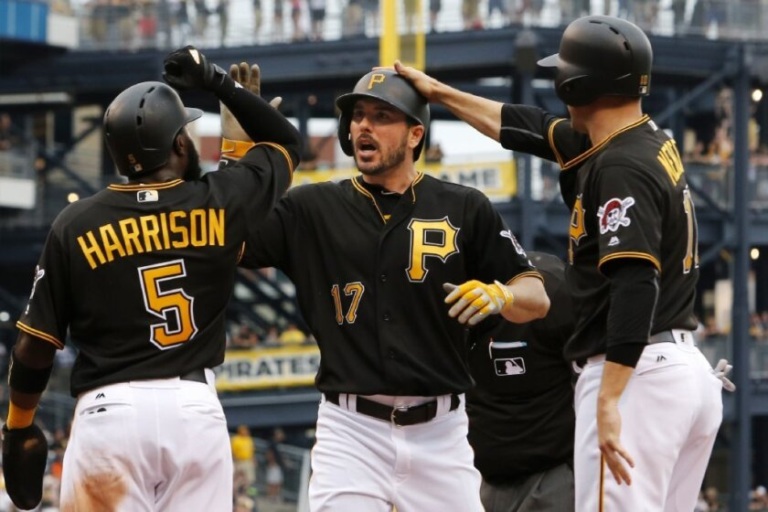 Pirates outfielder Matt Joyce (17) is greeted by teammates Josh Harrison (5) and Jordy Mercer after hitting a three-run home run against the Angels on Saturday.