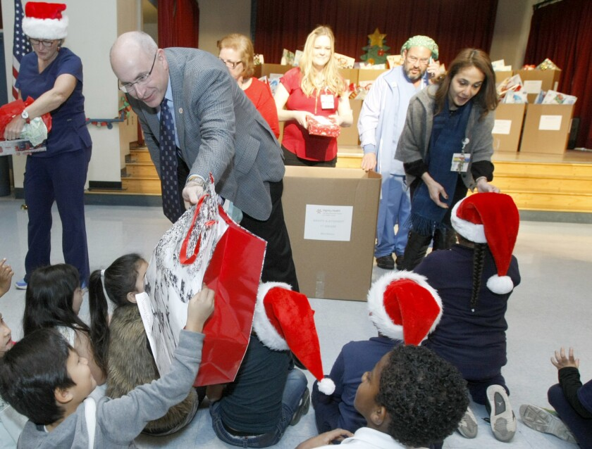 Wayne Herron, left, vice president of philanthropy for the Glendale Memorial Health Foundation, passes out a gift bag to a first-grade Cerritos Elementary School student. About 400 students at the school were surprised with gifts from Dignity Health Glendale Memorial Hospital employees.