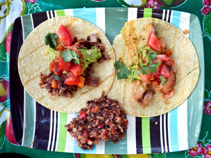 """This """"gourmet"""" do-it-yourself camping dinner includes Spanish rice and chicken tacos with guacamole, fresh tomatoes, grated cheese and cilantro."""