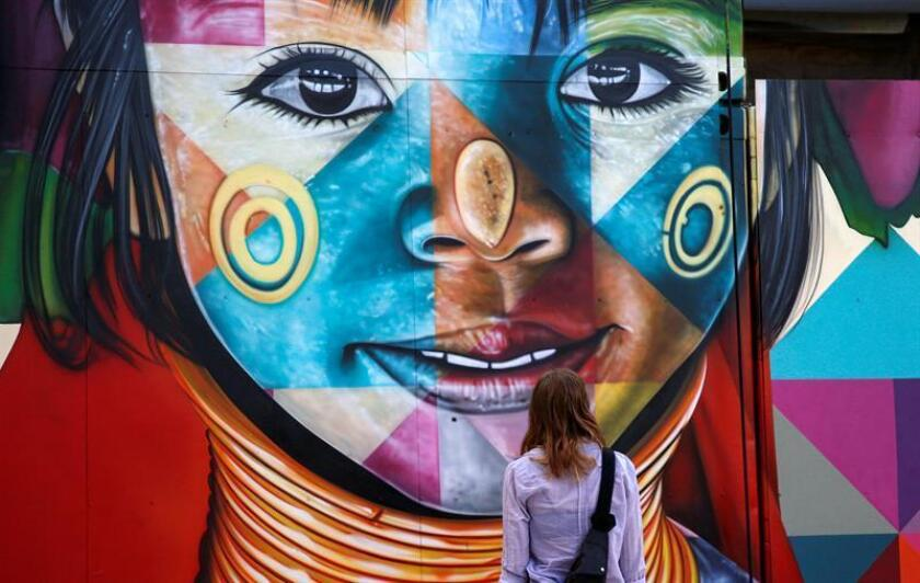 A woman looks at the latest works by Brazilian street artist Eduardo Kobra in the Wynwood district during Art Basel in Miami, Florida, USA, 06 December 2018. Art galleries and artists from all over the world descend on Miami for the event which is considered one of the world's largest art festivals with art events throughout the city. EPA-EFE/RHONA WISE