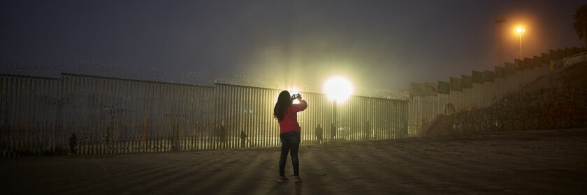 A woman uses her phone to record the border wall along the beach in Tijuanao.