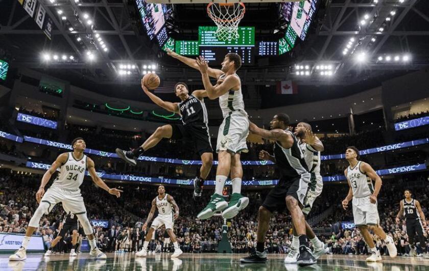 El guardia de los San Antonio Spurs Bryn Forbes (L) dispara en el centro de Milwaukee Bucks Brook Lopez (C) durante el juego de la NBA entre los San Antonio Spurs y los Milwaukee Bucks en el Fiserv Forum en Milwaukee, Wisconsin, EE. UU., 24 de noviembre de 2018. (Baloncesto, Estados Unidos) EFE