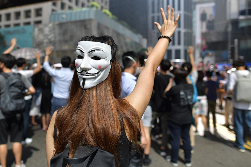 A woman with a Guy Fawkes mask takes part in a protest in Hong Kong on Friday.