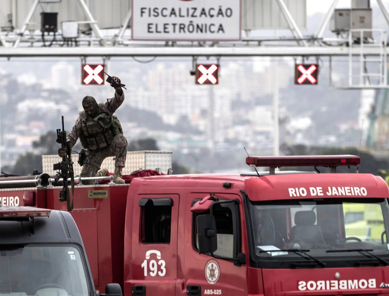 A police sniper celebrates after fatally shooting a hijacker who was threatening passengers on a bus in Rio de Janeiro on Tuesday. An armed man hijacked a bus and kept passengers and the driver as hostages while he threatened to burn the vehicle with gas.