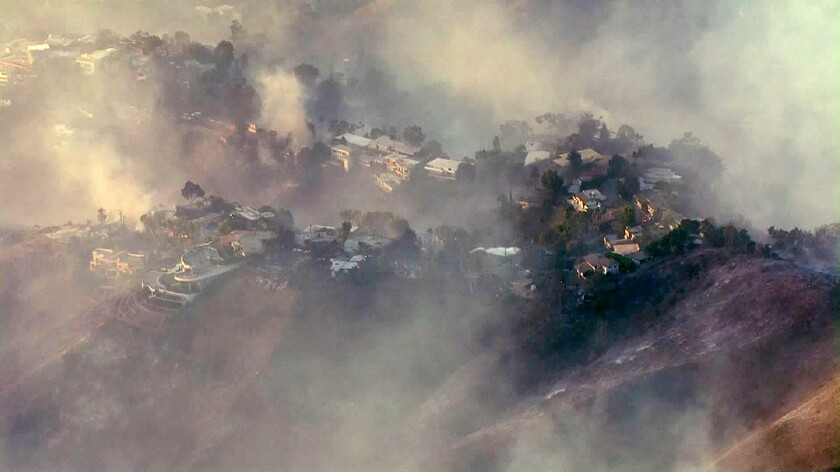 An aerial view of homes shrouded in smoke from the Getty fire.