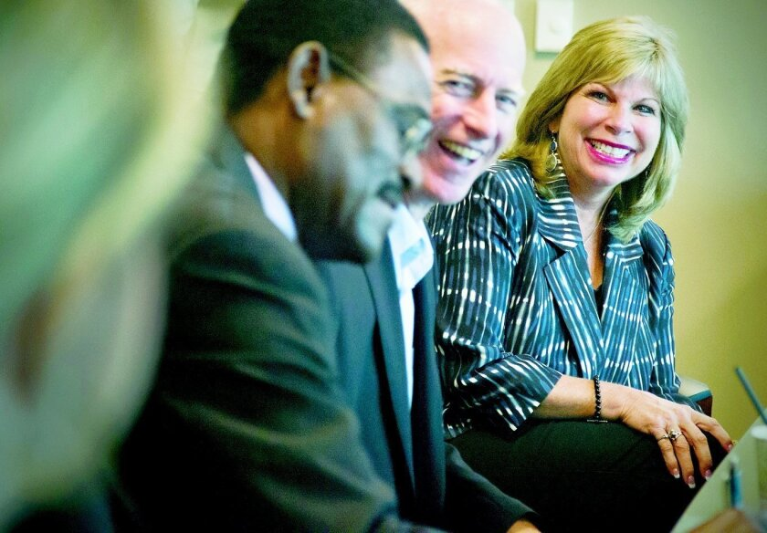 Mary Ann McGarry, president and CEO at Guild Mortgage, with Jim Madsen, executive vice president of servicing, (center) and Conrad Ottey, loan service manager, at a customer service training.  Howard Lipin • U-T