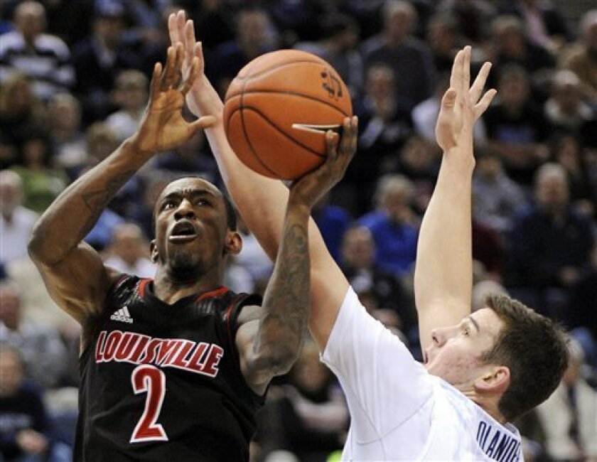 Louisville's Russ Smith (2) drives to the basket past Connecticut's Tyler Olander during the first half of an NCAA college basketball game in Hartford, Conn., Monday, Jan. 14, 2013. (AP Photo/Fred Beckham)