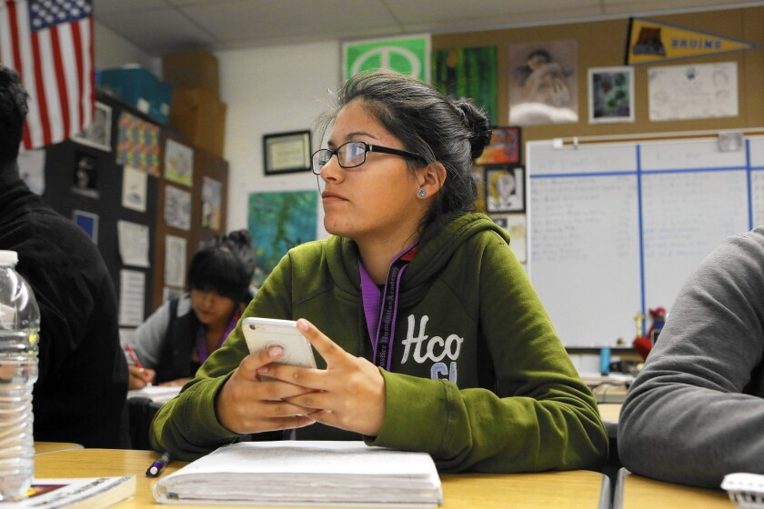 """Kimberly Ceballos, a student in English teacher Priscilla Farinas' class at Social Justice Humanitas Academy in San Fernando, uses her cellphone as part of a lesson on """"The Great Gatsby."""""""