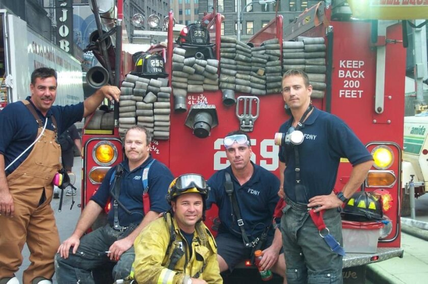 Rancho Santa Fe fire Capt. W. Chris Mertz, yellow jacket, poses with FDNY crews in 2001 while responding to 9/11.