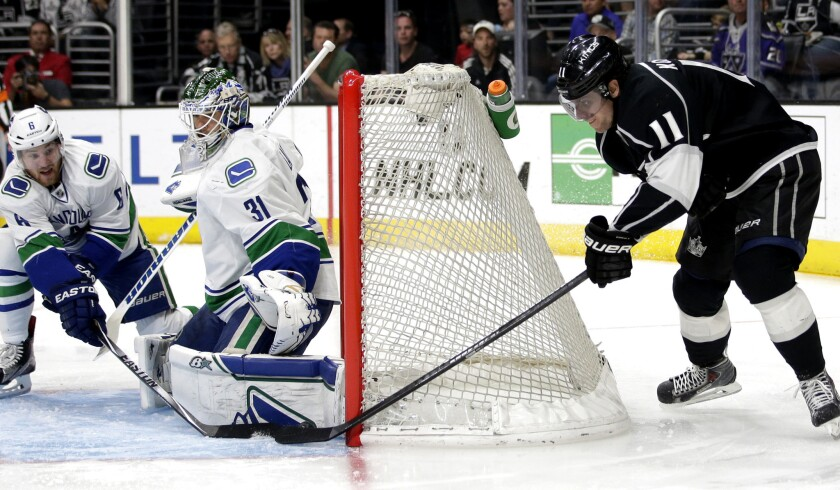 Kings center Anze Kopitar (11) tries to score on a wrap-around shot against Canucks goalie Eddie Lack in the second period.
