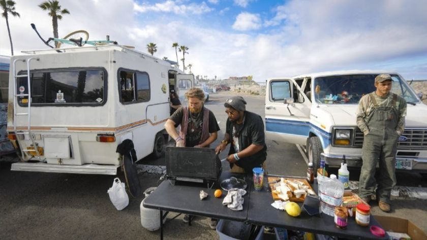 Residents of the white and blue Econoline van, left, prepare a breakfast of donated food on a butane range. Their street names, from left, Noodle, Oak and Noah.