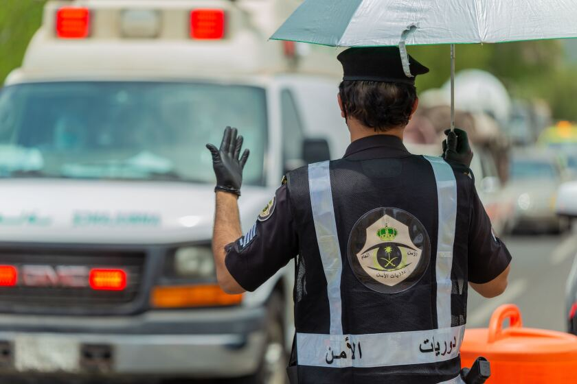 Saudi security officer motions at a checkpoint in the Mecca region