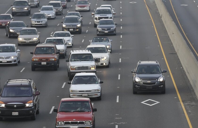 In this photo taken Feb. 4, 2015 photo a vehicle in the High Occupancy Vehicle lane, on right, passes lines of slow moving cars on Southbound Highway 99 in Sacramento, Calif. Gov. Jerry Brown wants to slash gasoline consumption in half by 2030, which would also drain the gas tax revenue used to rep