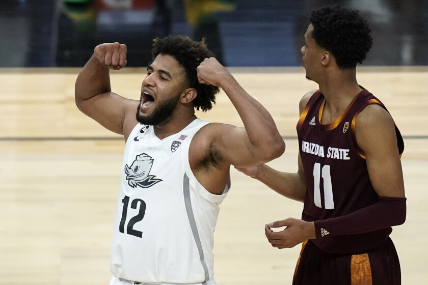 Oregon's LJ Figueroa (12) celebrates after a play against Arizona State during the second half of an NCAA college basketball game in the quarterfinal round of the Pac-12 men's tournament Thursday, March 11, 2021, in Las Vegas. (AP Photo/John Locher)