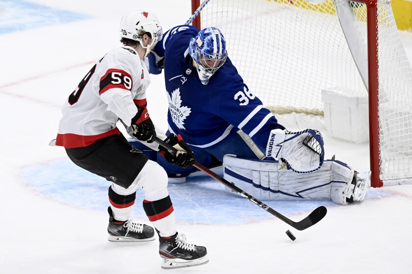 Ottawa Senators left wing Alex Formenton (59) looks for an opening on Toronto Maple Leafs goaltender Jack Campbell (36) during the first period of an NHL hockey game Saturday, April 10, 2021, in Toronto. (Frank Gunn/The Canadian Press via AP)