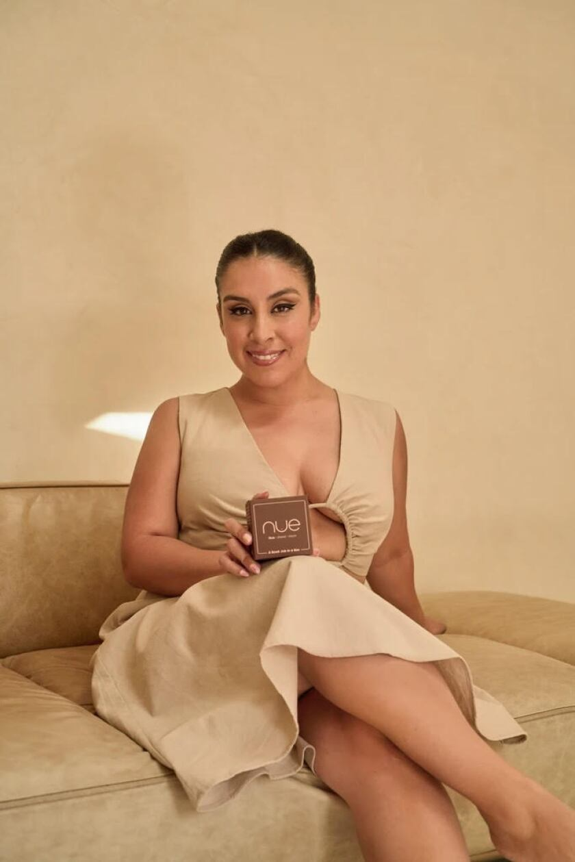 Stephanie Montes sits on a couch holding a carved block.