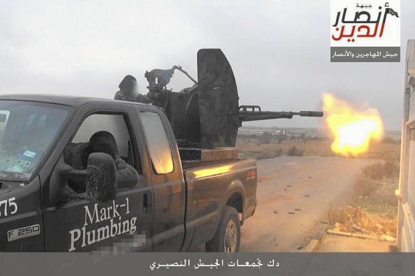 Mark Oberholtzer was assured by a Houston dealership that the decals would be removed from his old work truck when he traded it in. Now the truck carries a rebel group's antiaircraft gun in Syria, but still has Oberholtzer's business name and work number on the door.