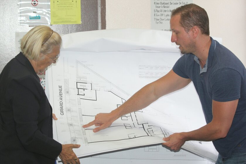 Philip Quatrino (right) of PQ Design Studio shows Development Permit Review Committee member Angeles Liera new plans to develop commercial and residential units on the rear lot of Vons grocery store.