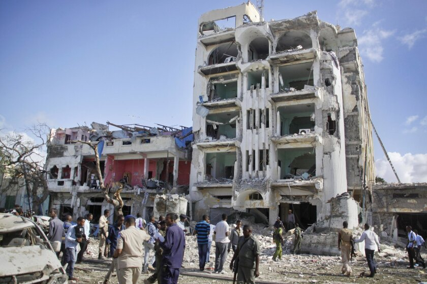 Security forces examine the scene after a bomb attack on Ambassador Hotel in Mogadishu, Somalia, Thursday, June 2, 2016. Somalia's Islamic extremist rebels, al-Shabab, stormed the hotel, often frequented by government officials and business executives, killing people and taking a number of hostages