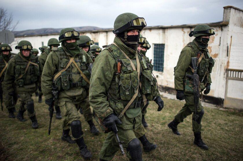 Armed men in uniform walk outside a Ukrainian military unit's territory Sunday in the village of Perevalnoye, outside Simferopol, in Ukraine's Crimea region.