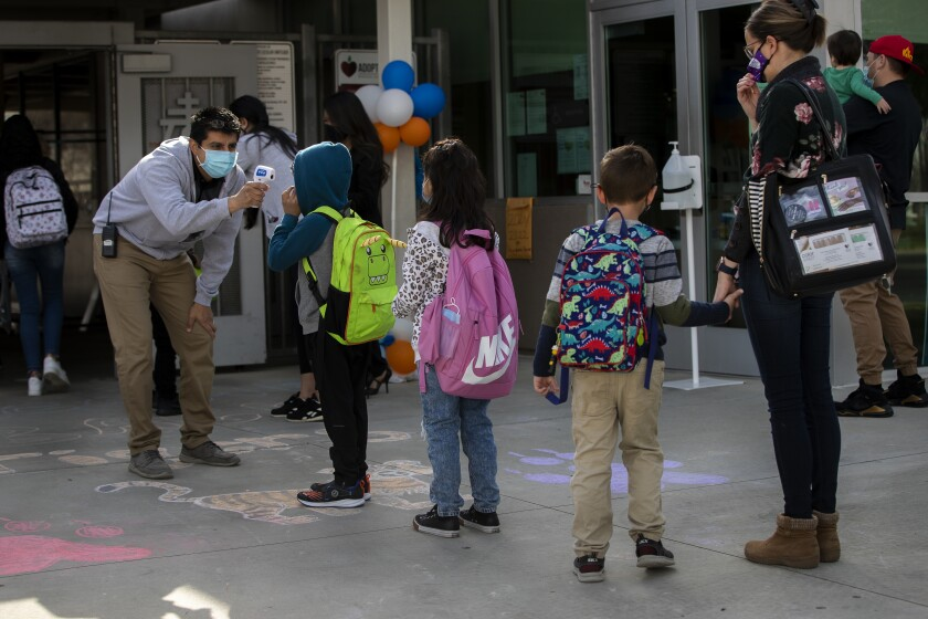 Kindergarteners get their temperatures checked as they return to school in Riverside.