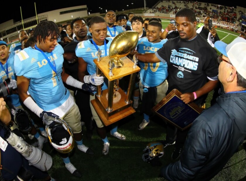 Locke coach Michael Klyce and his football team with a trophy.