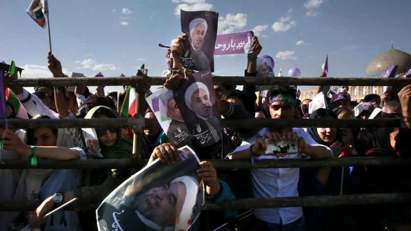 Supporters of Iranian President Hassan Rouhani hold signs at a pre-election rally in Isfahan, Iran.