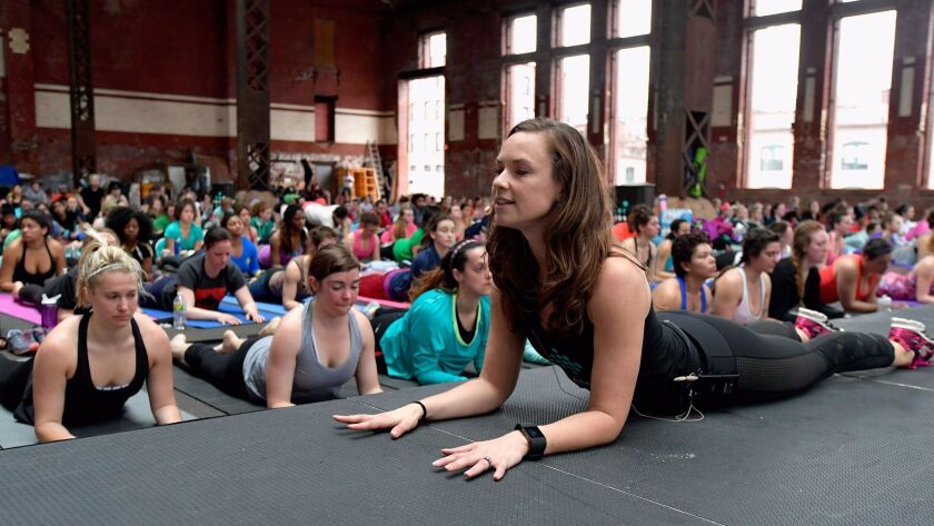 Cara Gilman wears a Fitbit tracker as she leads a yoga workout in Boston. A new study assessing four wristband fitness trackers found that none of them were good at tracking heart rate when users were moving while exercising.