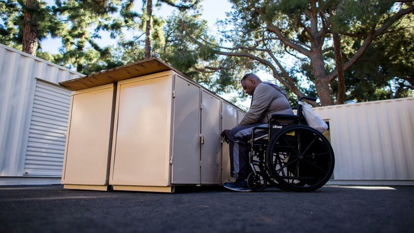 Wayne Ross gets personal items out of his locker built by the city of Pomona for homeless residents.