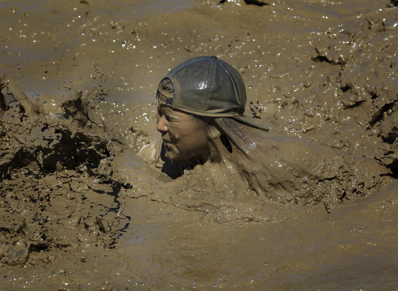 One runner makes her way through the final obstacle the Mud Pit before crossing the finish line at the annual 10K Camp Pendleton Mud Run on Sunday.