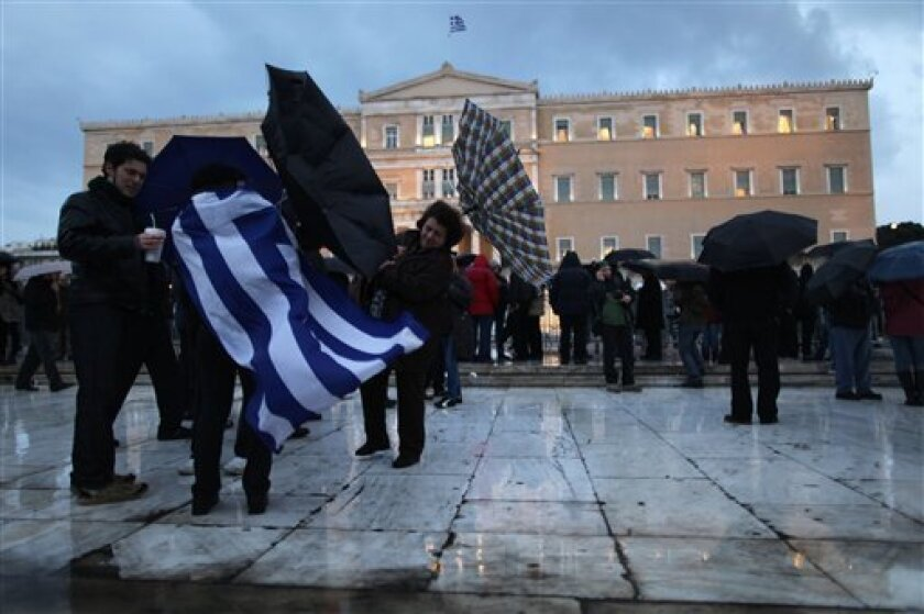 Protesters, one with a Greek flag, struggles to hold umbrellas in a storm, in front of the Greek parliament during a Wednesday protest in Athens over  a batch of emergency laws that will further cut incomes and state spending.