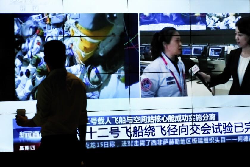La silueta de un hombre frente a una pantalla que muestra un noticiero de la televisora CCTV con un reporte sobre el regreso de astronautas chinos a la Tierra, en un centro comercial en Beijing, el 16 de septiembre de 2021. (AP Foto/Andy Wong)
