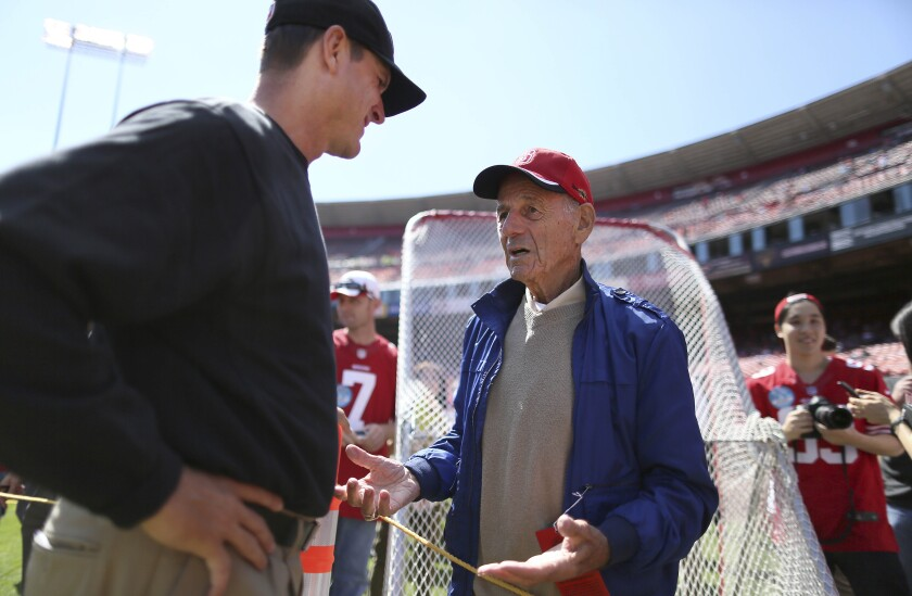 San Francisco 49ers head coach Jim Harbaugh, left, talks to former coach Dick Coury in 2013.