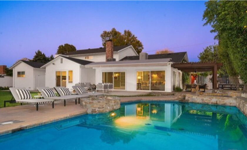 Gated and landscaped, the nearly half-acre property holds a two-story home and a swimming pool out back.