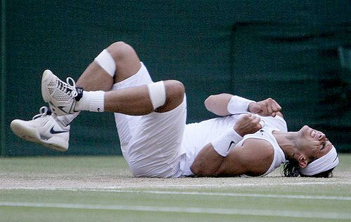 Rafael Nadal falls to the court after Roger Federer netted a forehand on match point Sunday in the men's final at Wimbledon.