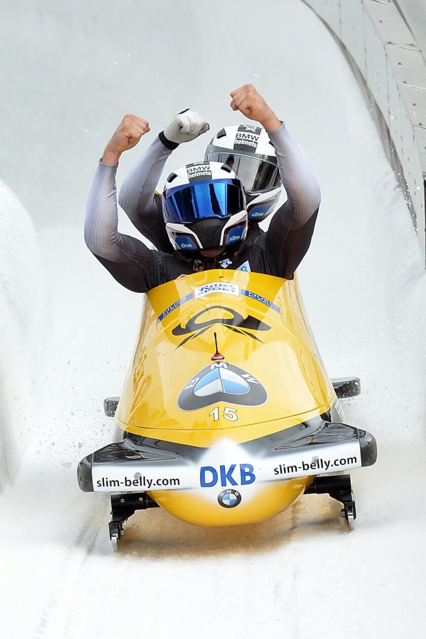 Germany's second placed  Johannes Lochner and Joshua Bluhm  celebrate after their final run of the two-man bob race at the Bob World Championships  in Igls, near Innsbruck, Austria, on Sunday, Feb. 14, 2016.  (AP Photo/Kerstin Joensson)