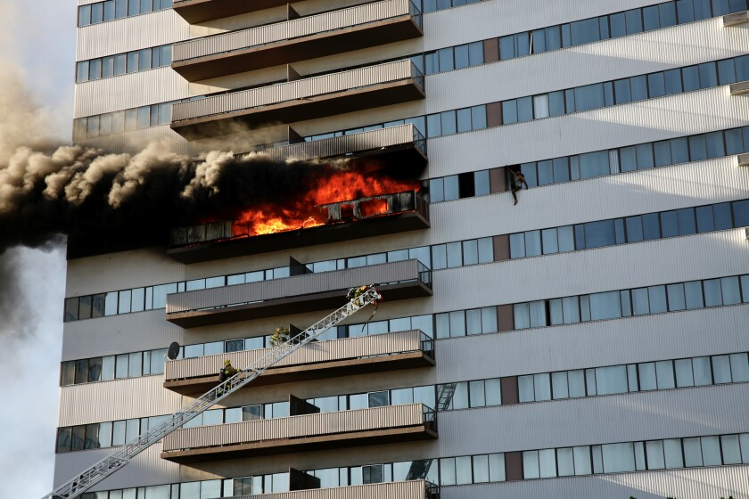 A resident tries to escape the flames as Los Angeles firefighters battle a large blaze at the Barrington Plaza apartments. A 19-year-old man died from injuries suffered in the fire.