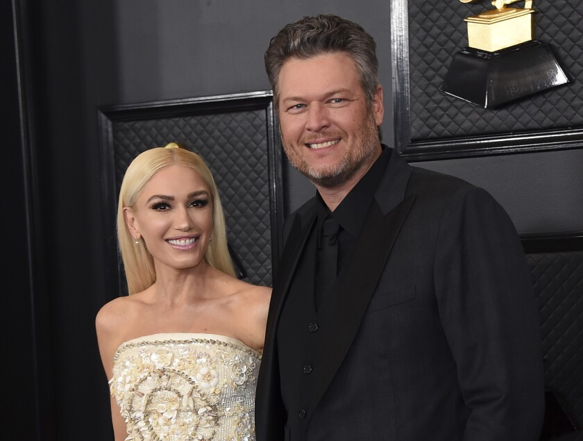 """FILE - In this Jan. 26, 2020, file photo, Gwen Stefani, left, and Blake Shelton arrive at the 62nd annual Grammy Awards in Los Angeles. """"The Voice"""" coaches Stefani and Shelton celebrated their nuptials over the Fourth of July holiday during a weekend wedding in Oklahoma. Images were posted Monday, July 5, 2021, of their wedding. (Photo by Jordan Strauss/Invision/AP, File)"""