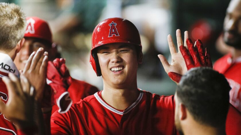 Los Angeles Angels' Shohei Ohtani smiles as he is greeted in the dugout by teammates after scoring o