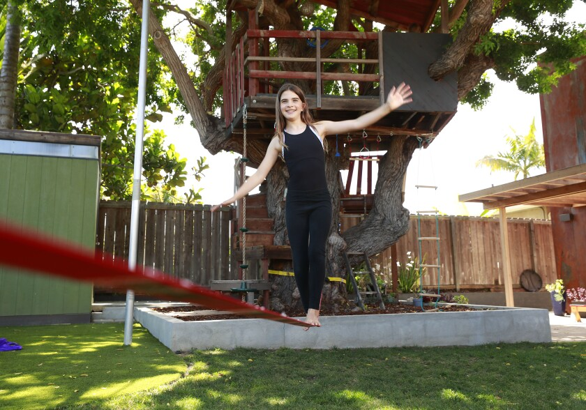Miriam practices balancing on a slackline, which is anchored and suspended low off the ground.