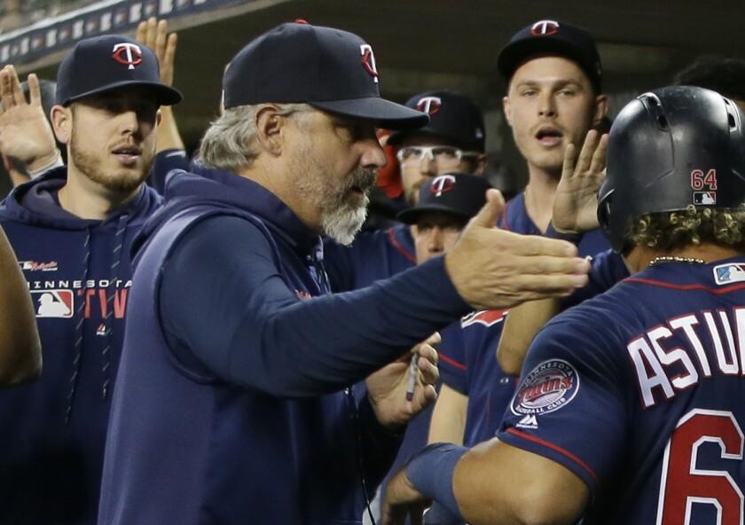 Minnesota Twins bench coach Derek Shelton congratulates a player.