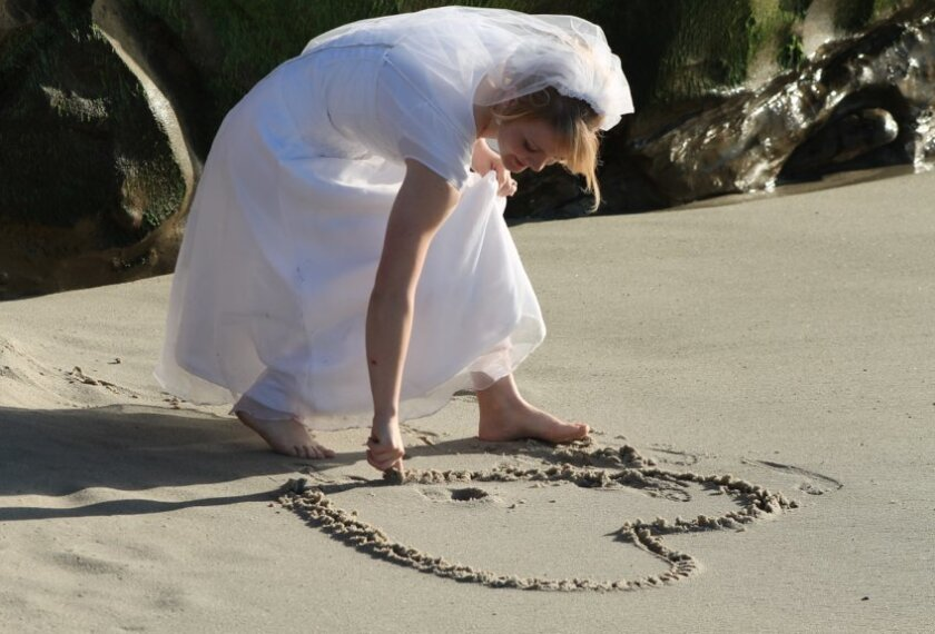 A bride from Provo, Utah creates a heart in the sand at Windansea on Feb. 16th, where the temperature rose into the mid-70s.