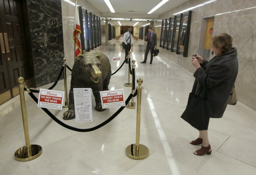 """In another coronavirus precaution, California officials cordoned off the sculpture of a bear outside the office of Gov. Gavin Newsom, at the Capitol in Sacramento, Calif., Wednesday, March 11, 2020. The sculpture was purchased by former Gov. Arnold Schwarzenegger and was quickly nicknamed """"Bacteria Bear,"""" after it became a favorite backdrop for photographs and selfies by school children and other Capitol visitors. (AP Photo/Rich Pedroncelli)"""