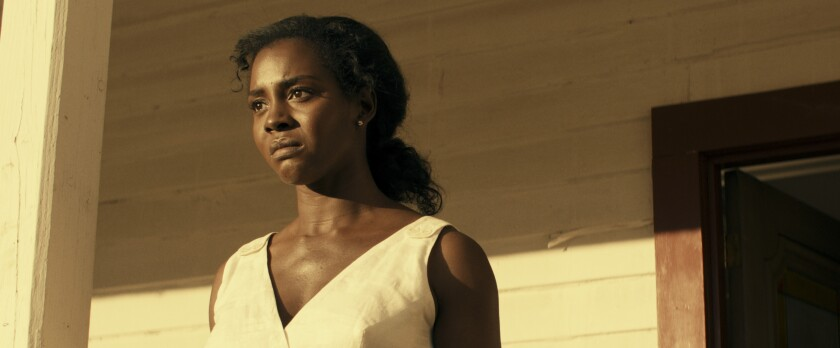 A woman in a white dress frowning on her front porch