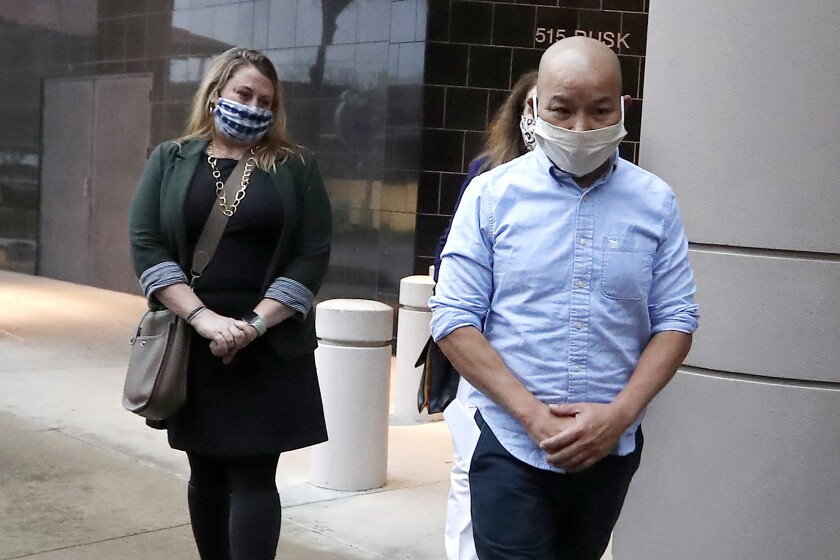 Former Houston police Officer Tam Pham walks out of the Federal Courthouse downtown in Houston with two women.